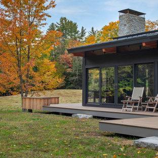 Exemple d'une petit façade de maison grise rétro de plain-pied avec un revêtement en panneau de béton fibré, un toit à deux pans et un toit en shingle.