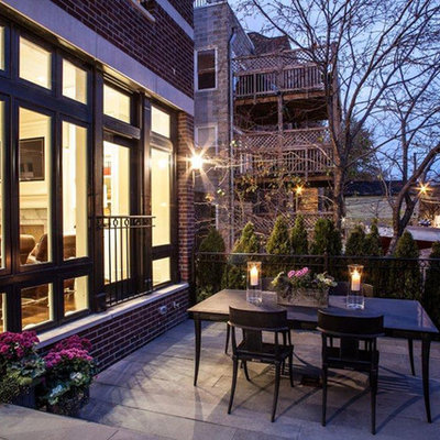 Large traditional brown three-story brick exterior home idea in Chicago