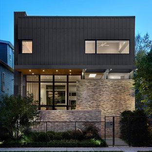 Пример оригинального дизайна: двухэтажный, серый дом среднего размера в современном стиле с облицовкой из ЦСП и плоской крышей
