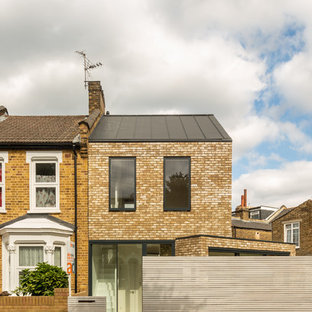 Inspiration for a brown contemporary two floor brick detached house in Vancouver with a pitched roof and a metal roof.
