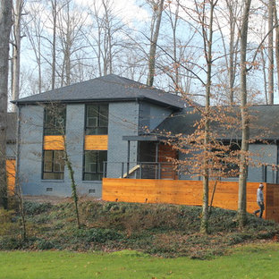 Example of a large minimalist gray three-story exterior home design in Raleigh with a clipped gable roof