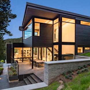 Неиссякаемый источник вдохновения для домашнего уюта: большой, трехэтажный, стеклянный, коричневый частный загородный дом в современном стиле с односкатной крышей и зеленой крышей