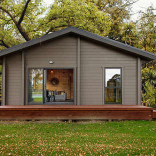 Imagen de fachada de casa gris, nórdica, pequeña, de una planta, con revestimiento de madera, tejado a dos aguas y tejado de metal