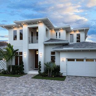 Imagen de fachada de casa beige, actual, de tamaño medio, de dos plantas, con revestimiento de estuco y tejado de teja de barro