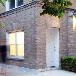 Ejemplo de fachada de piso beige, ecléctica, de tamaño medio, de una planta, con revestimiento de ladrillo y tejado plano