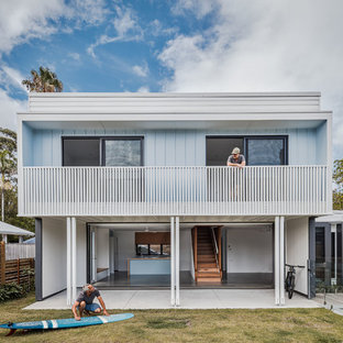 This is an example of a beach style two-storey blue house exterior in Gold Coast - Tweed with a flat roof.
