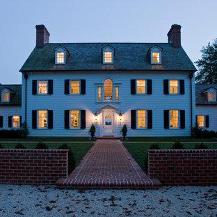 Cette photo montre une grande façade en bois blanche chic à deux étages et plus avec un toit à deux pans.