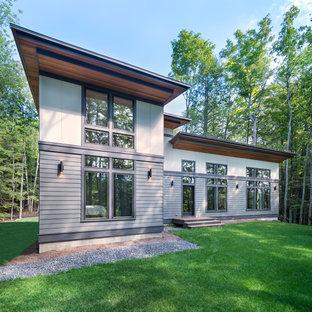 Cette photo montre une façade de maison grise tendance à un étage et de taille moyenne avec un revêtement en panneau de béton fibré et un toit en appentis.