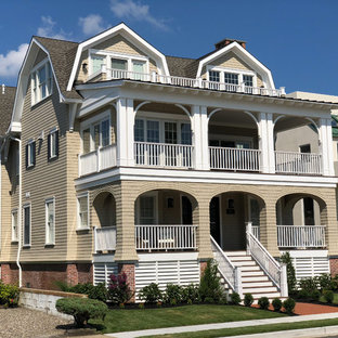 Example of a large beach style beige three-story wood house exterior design in Philadelphia with a gambrel roof and a shingle roof