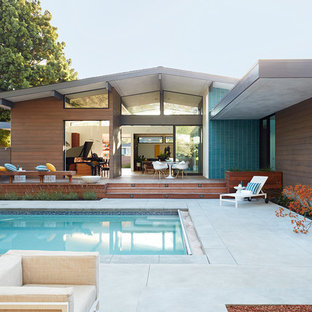 Cette image montre une façade de maison multicolore vintage de plain-pied avec un revêtement mixte et un toit à deux pans.