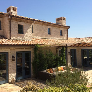 Inspiration for a large southwestern beige two-story stone exterior home remodel in San Francisco with a tile roof