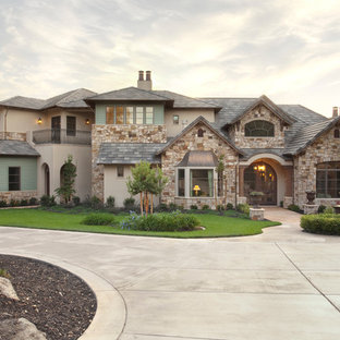 Example of a french country beige two-story stone flat roof design in Sacramento