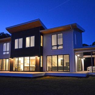 На фото: двухэтажный, белый частный загородный дом среднего размера в современном стиле с облицовкой из металла, крышей-бабочкой, металлической крышей, серой крышей и отделкой планкеном