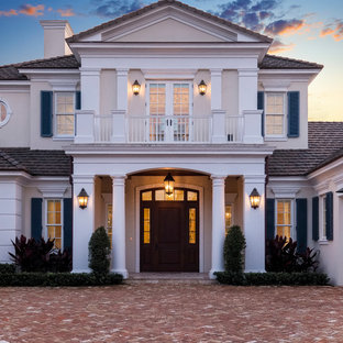 Large elegant beige two-story stucco house exterior photo in Other with a tile roof
