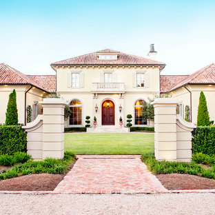 Example of a tuscan beige two-story stucco exterior home design in New Orleans with a hip roof