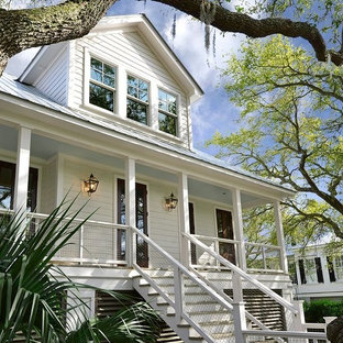 Large beach style white two-story concrete fiberboard house exterior idea in Charleston with a hip roof and a metal roof