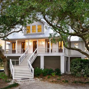 Diseño de fachada de casa blanca, marinera, grande, de dos plantas, con revestimiento de aglomerado de cemento, tejado a cuatro aguas y tejado de metal