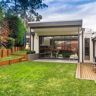 Imagen de fachada gris, moderna, pequeña, de una planta, con revestimiento de ladrillo y tejado plano
