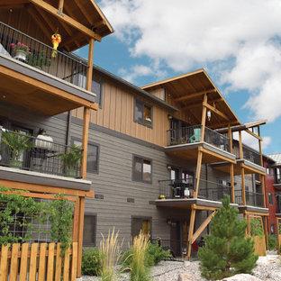Imagen de fachada marrón, contemporánea, extra grande, de tres plantas, con revestimiento de madera