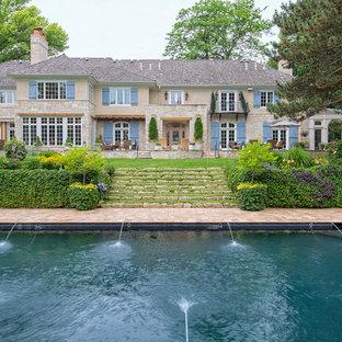 Idee per la facciata di una casa beige classica a due piani con tetto a padiglione