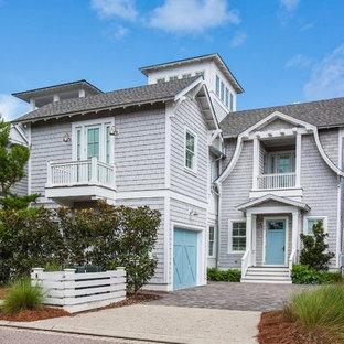 Coastal gray three-story wood exterior home photo in Miami with a shingle roof