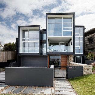 Contemporary black house exterior in Sydney with three or more storeys and a flat roof.
