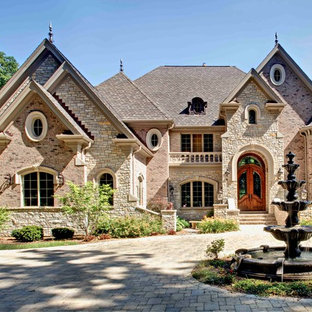 Large elegant beige two-story brick exterior home photo in Chicago with a shingle roof