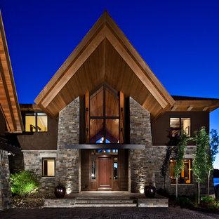 Immagine della facciata di una casa unifamiliare grande marrone rustica a tre o più piani con rivestimento in pietra, tetto a padiglione e copertura a scandole