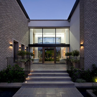 Example of a large minimalist white two-story brick exterior home design in Other