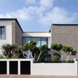 Large modern white two-story brick flat roof idea in Other