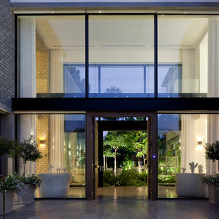 Large modern white two-story brick exterior home idea in Other