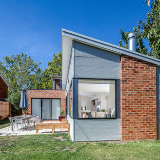 This is an example of a mid-sized contemporary one-storey grey house exterior in Canberra - Queanbeyan with metal siding and a shed roof.