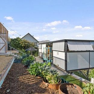 Modelo de fachada de casa gris, bohemia, pequeña, de una planta, con revestimiento de metal, tejado plano y tejado de metal