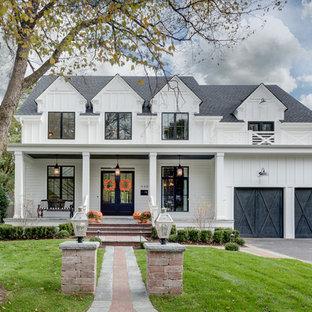 Immagine della facciata di una casa unifamiliare grande bianca country a due piani con rivestimento in legno e copertura a scandole