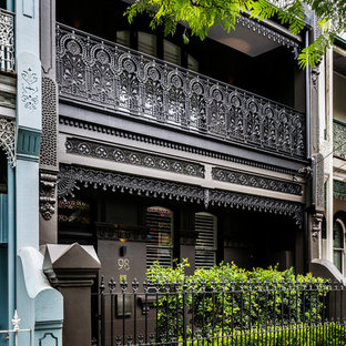 Inspiration for a mid-sized traditional brick grey townhouse exterior in Sydney with three or more storeys, a gable roof and a metal roof.