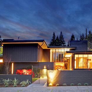 Cette image montre une très grand façade de maison grise vintage à un étage avec un revêtement mixte et un toit plat.
