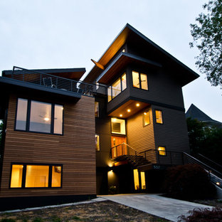 Inspiration for a large modern green three-story wood exterior home remodel in Seattle with a shed roof