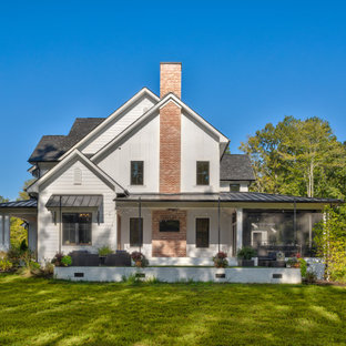Large country white two-story concrete fiberboard exterior home photo in Charlotte with a mixed material roof