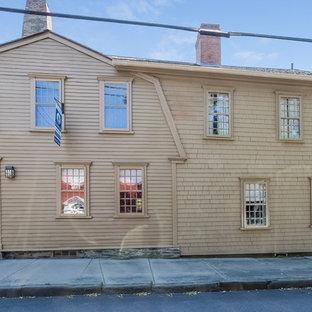 Foto de fachada beige con revestimiento de madera y tejado a doble faldón
