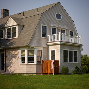Photo of a mid-sized arts and crafts two-storey beige exterior in Portland Maine with wood siding and a gambrel roof.