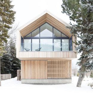 Foto de fachada nórdica con revestimiento de madera y tejado a dos aguas
