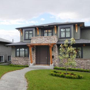 Пример оригинального дизайна: большой, двухэтажный, зеленый частный загородный дом в современном стиле с облицовкой из камня, двускатной крышей и крышей из гибкой черепицы