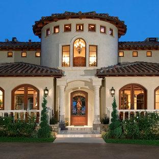 Diseño de fachada beige, mediterránea, grande, de dos plantas, con revestimiento de estuco