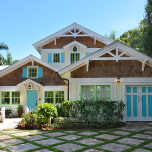 Example of a mid-sized coastal yellow two-story wood gable roof design in Tampa