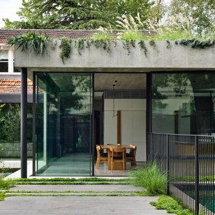 Идея дизайна: большой, одноэтажный, серый частный загородный дом с облицовкой из бетона, плоской крышей и зеленой крышей