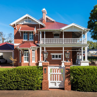 Large traditional two-storey brick red house exterior in Adelaide with a hip roof and a metal roof.