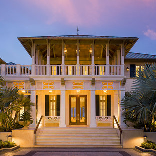 Island style white two-story exterior home photo in Miami with a hip roof