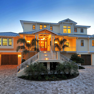 Large beach style beige three-story wood exterior home idea in Other