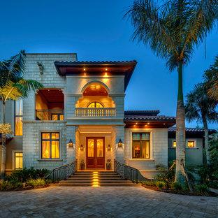 Diseño de fachada beige, tropical, de dos plantas, con revestimientos combinados