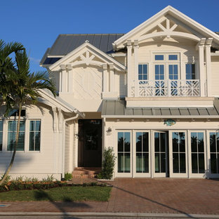 Inspiration for a huge tropical white two-story mixed siding exterior home remodel in Miami
